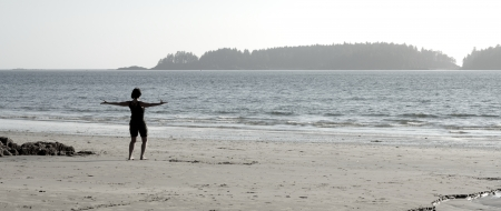 Woman doing Tai Chi exercises on a beach at the Pacific Ocean