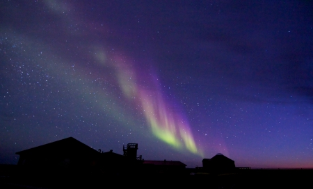 Amazing Aurora Borealis, or Northern Lights, over a building silhouette at Hudson Bay, near Churchill, Manitoba, in summer Stock Photo