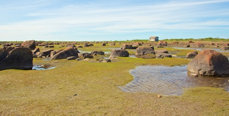 View over the stone desert of Hudson Bay, Canada, during low tide with rocks and stones in the tidal pools and a cabin in the background Stock Photo