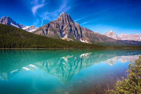 View on Hector Lake with a mountain reflecting in the quiet waters