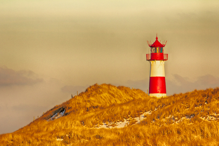 Beautiful sand dune scene with a lighthouse  photo