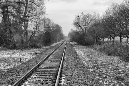 Empty railroad track leading into the hazy distance on a winter evening, monochromatic version photo