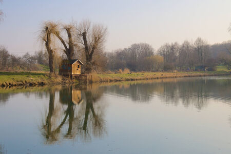 Small fishing hut under willow trees at a quiet lake