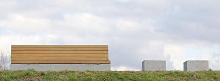grassy knoll: Modern stone and wood bench and two additional seats on a grassy knoll