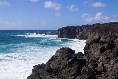 Black volcanic lava rocks at wild coastline of Los Hervideros on Lanzarote island, Spain
