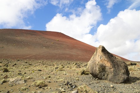volcano slope: Red colored volcano slope with a huge boulder in the foreground