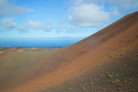 volcano slope: Colofred lava eatht on a volcano slope in Timanfaya national park, Lanzarote island, Spain