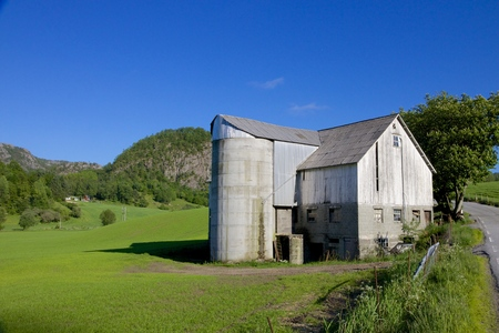 Old grain silo and barn next to a lush green meadow under the hills of Rogaland, Norway photo