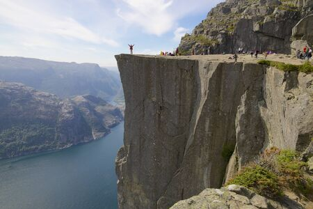 View over the world famous Preikestolen - or pulpit rock - over the Lysefjord, Norway, with a happy hiker showing his success photo