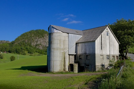 Old grain silo and barn next to a lush green meadow under the hills of Rogaland, Norway