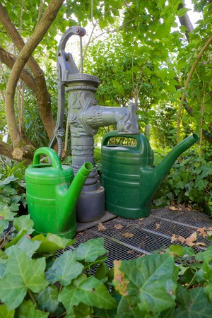 Traditional pump well with twi green watering cans in a green garden photo