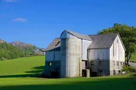 Old, shabby Norwegian farm house and grain silo on a lush green meadow