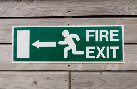 fire exit sign: Green fire exit sign on a wood panel wall of a public building Stock Photo