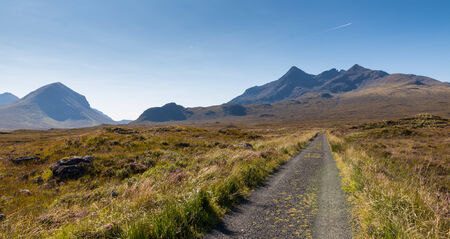 Gravel road leading towards the famous range of the Cuillin Hills on the Isle of Skye, Scotland