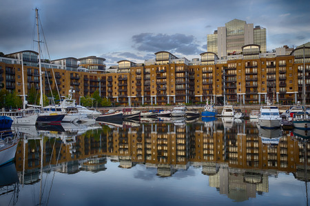 View onto exclusive apartment blocks at St. Katherine's dock, London, with boats and yachts anchoring in the foreground, HDR version
