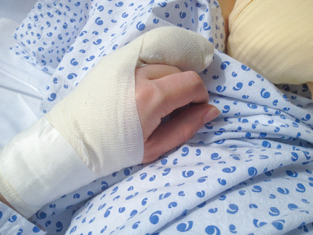 bone fracture: Swollen hand in bandages right after complicated surgery on the ring finger