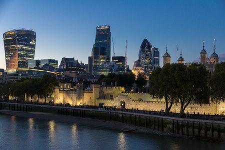 dungeons: View along the walls of the Tower of London with the modern city skyline in the background at night Editorial
