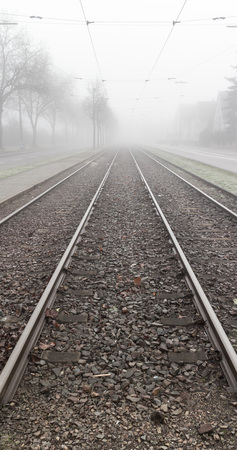 Railroad tracks leading into thick mysterious fog on a cold and wet winter day photo