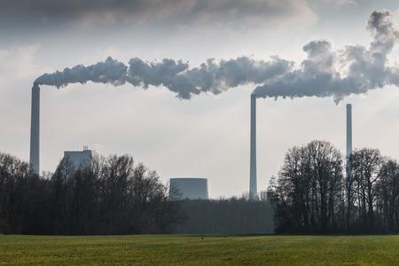 polluting: Huge factory chimneys polluting the air