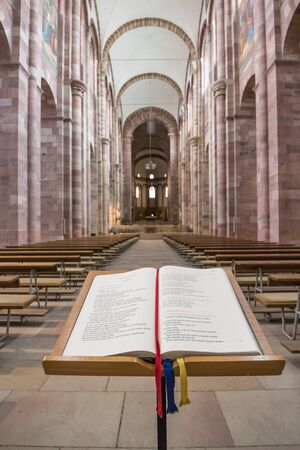 Impressions of the interior of famous Speyer Cathedral, Germany, a majestic building from the 13th century with a German Bible in the foreground Redactioneel
