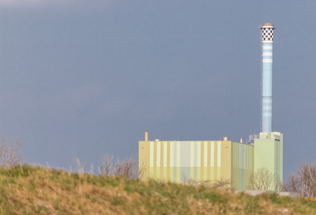 grassy knoll: Factory and power plant with a huge chimney shot over a grassy knoll along the River Rhine, Germany