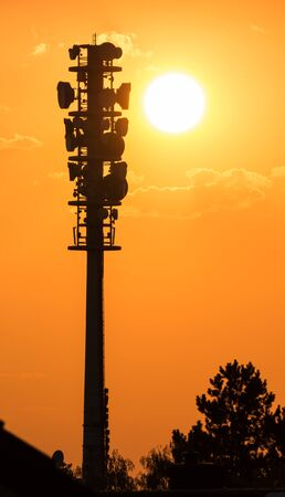 radio tower: Epic dusk scene with a huge radio tower silhouette in the glowing yellow sunset of a summer evening