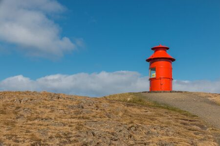 Cute little red lighthouse on a basalt island at the harbor of Stykkisholmur, Iceland Stock Photo