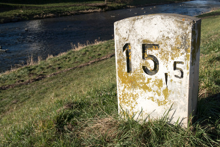 one lane road sign: Old milestone on a sunny and lush green meadow at the shore of a small river near Freiburg, Germany