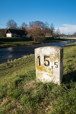 freiburg: Old milestone on a sunny and lush green meadow at the shore of a small river near Freiburg, Germany