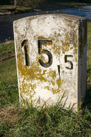 one lane roadsign: Old milestone on a sunny and lush green meadow at the shore of a small river near Freiburg, Germany