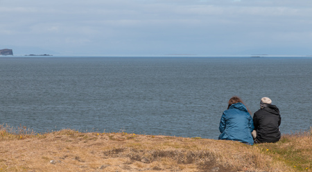 grassy knoll: Couple sitting on top of a grassy knoll above an Icelandic fjord on Snaefellsnes peninsula Stock Photo