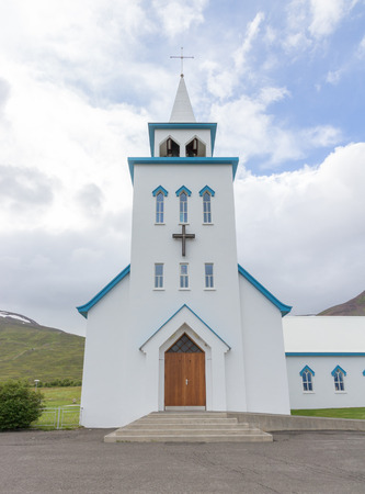 country church: Typical small wooden church in front of a dramatic mountain backdrop in the fishing village of Dalvik, Iceland