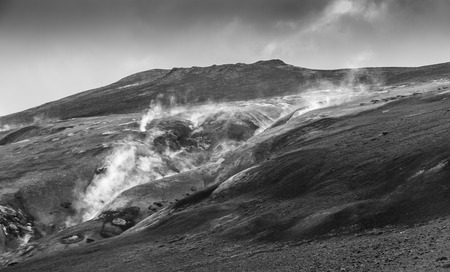 crater highlands: Steaming rim of a volcanic lava mountain in the Krafla region, Iceland, monochromatic version Stock Photo