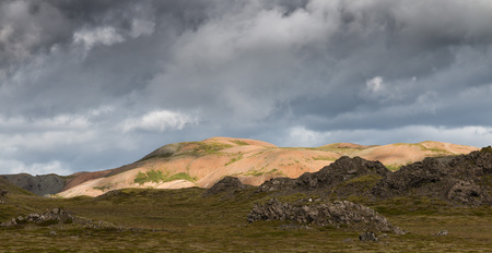 pano: Barren volcanic landscape with one hill sitting right in the sun at the southeast coast of Iceland