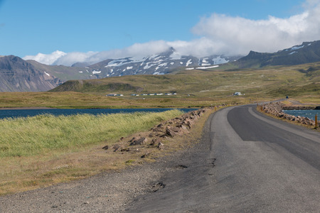 pano: Narrow gravel road leading over a fjord towards snow-covered mountains on Snaefellsnes peninsula, western Iceland Stock Photo