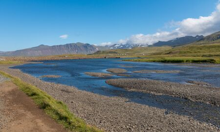 Lush green river landscape next to Kirkjufell mountain in northwestern Iceland Stock Photo