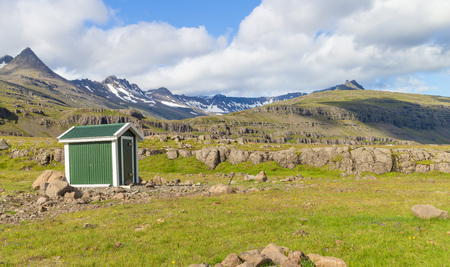 Lush green meadows and a little wooden hut with a backdrop of harsh volcanic snow-covered mountains in eastern Iceland