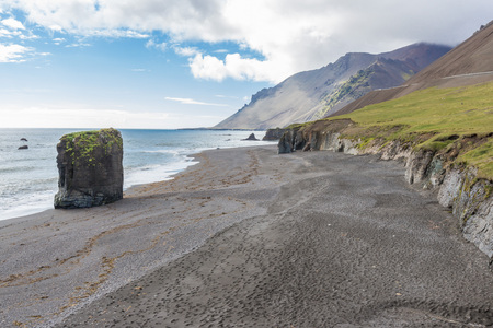 pano: Volcanic black sand beach with harsh rocks in Austurland, eastern Iceland
