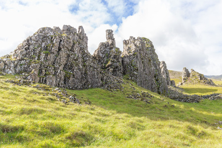 Rough rocks on grassy hills and lush green meadows in eastern Iceland