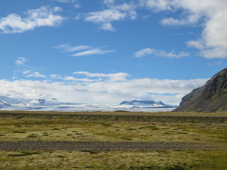 pano: Impressive volcano caldera on a glacier between mountains, covered in snow, southern Iceland