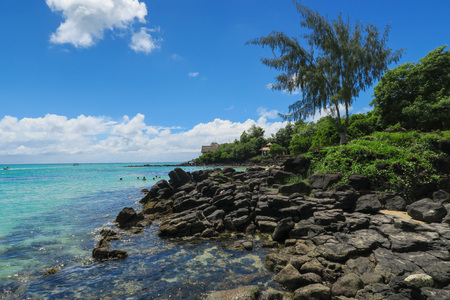 Lava rock beach on beautiful Mauritius island at the clear blue waters of the Indian Ocean Stock Photo