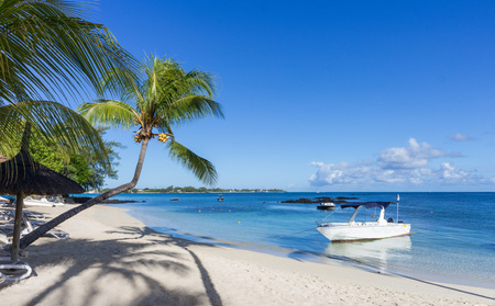 White sand beach on beautiful Mauritius island at the clear blue waters of the Indian Ocean with moored boats