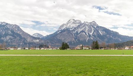 Road through the lush green meadows of Bavarian Allgau region near famous Castle Neuschwanstein, Germany
