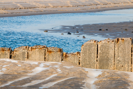 Old row of stones, built as a breakwater on the western beach of Sylt island, Germany Stock Photo