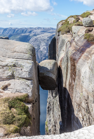 Famous Kjeragbolten boulder stuck between two granite cliffs on Kjerag mountain, a famous hike in Rogaland, Norway