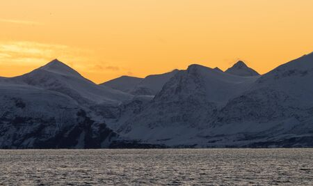 Epic Norwegian fjord and barren, snow covered mountains during sunset, far above the polar circle near Skjervoy