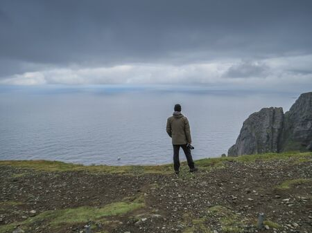 Lonely photographer standing at a rock cliff high above the arctic sea at North Cape, Norway