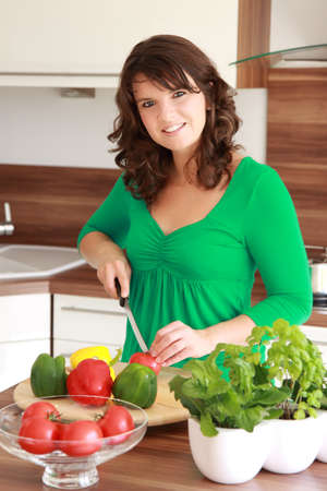 beautiful brunette woman cut the lettuce in the kitchen Stock Photo - 11040732