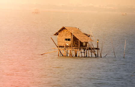 Bamboo houses,Bamboo huts on the calm lake .Wooden house on the sea in sunset time. Stock Photo