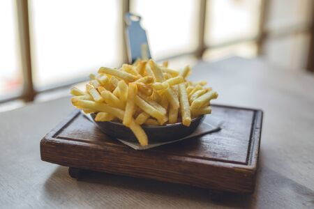 French fries in frying pan on wooden table Banque d'images